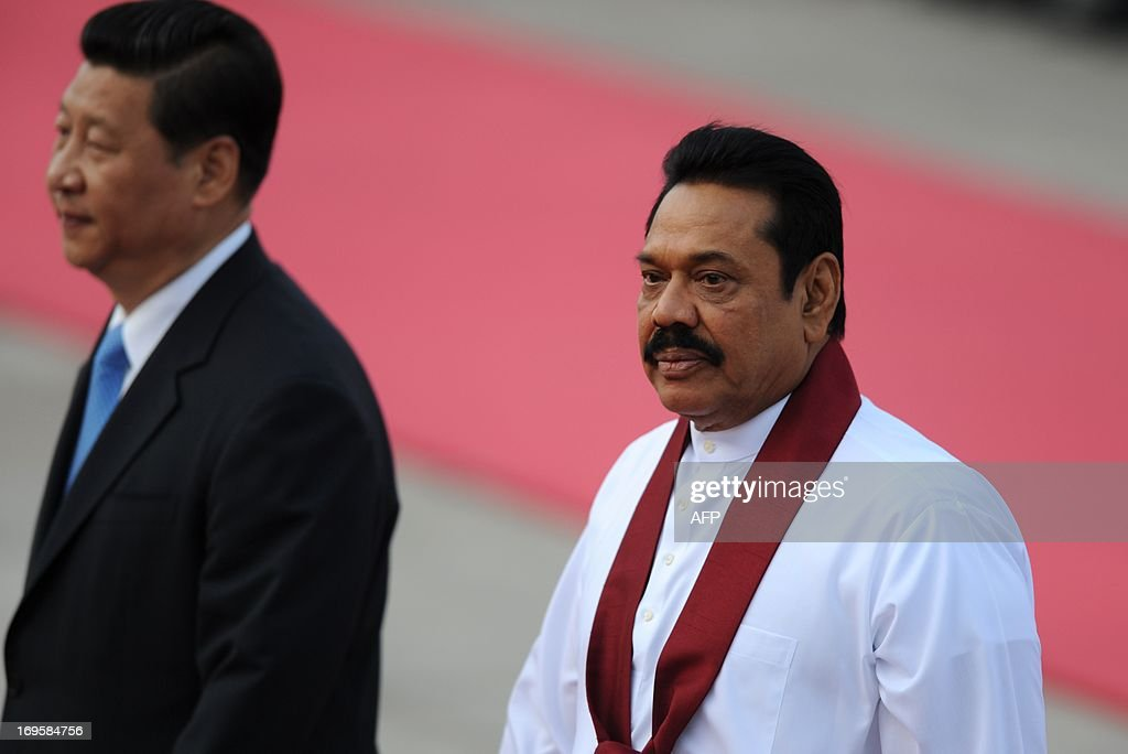 Sri Lankan President Mahinda Rajapaksa (R) and Chinese President Xi Jinping (L) inspect Chinese honour guards during a welcoming ceremony outside the Great Hall of the People in Beijing on May 28,2013. Mahinda Rajapaksa is on a two-day visit to China. AFP PHOTO/WANG ZHAO
