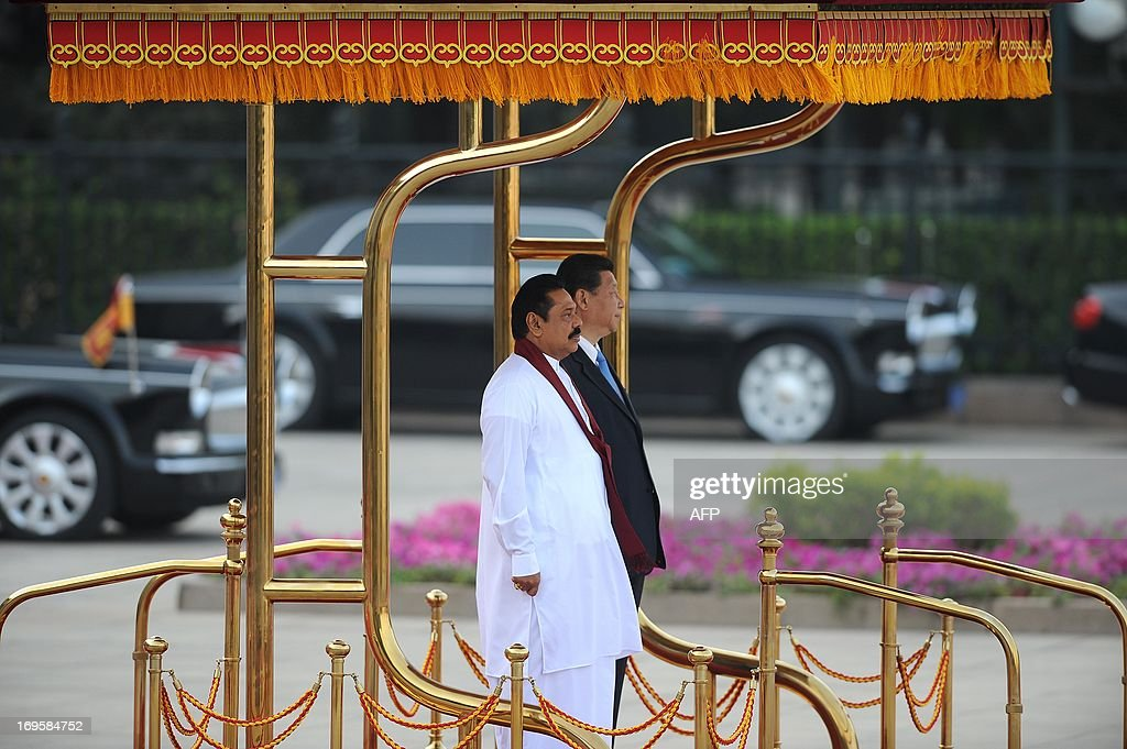 Sri Lankan President Mahinda Rajapaksa (L) and Chinese President Xi Jinping (R) prepare to inspect Chinese honour guards during a welcoming ceremony outside the Great Hall of the People in Beijing on May 28,2013. Mahinda Rajapaksa is on a two-day visit to China. AFP PHOTO/WANG ZHAO