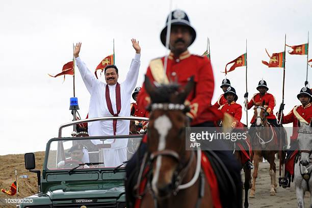 Sri Lankan President Mahinda Rajapaksa is escorted by mounted policemen as he waves at supporters from the rear of an open vehicle during a...