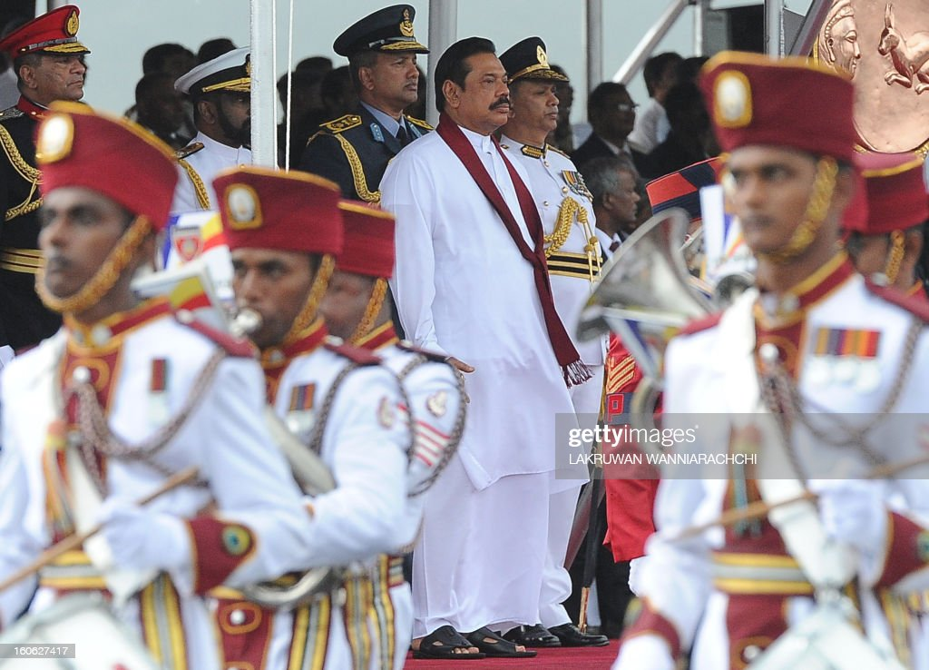 Sri Lankan President Mahinda Rajapakse (C) watches a military parade during the country's 65th Independence Day celebrations in the northeastern town of Trincomalee on February 4, 2013. Sri Lanka marked its freedom anniversary with a thinly veiled denunciation of Western moves to pass a new resolution against the island at the UN Human Rights Council.