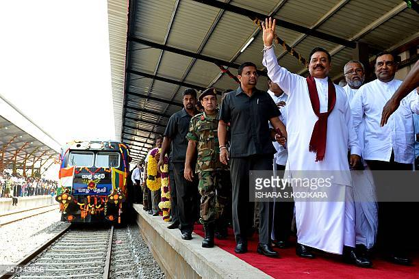 Sri Lankan President Mahinda Rajapakse gestures to acknowledge cheers at the rebuilt Jaffna railway station on October 13 as he arrives to officiate...