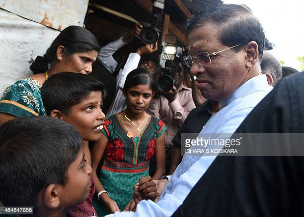 Sri Lankan President Maithripala Sirisena speaks with minority Tamil residents in the eastern town of Muttur on August 22 2015 Sirisena visited the...