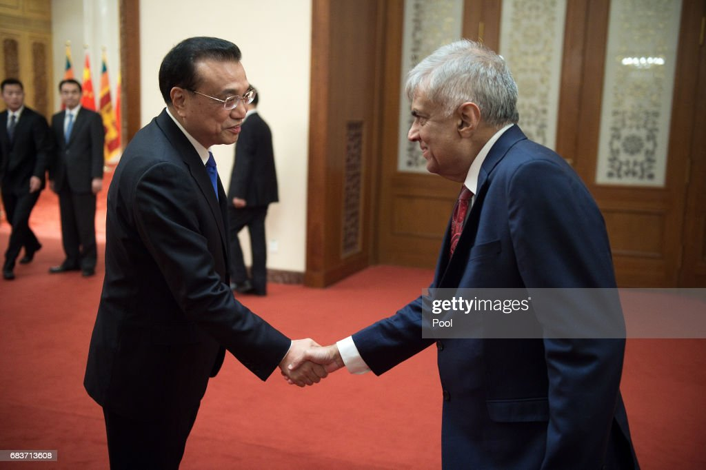 Sri Lankan Prime Minister Ranil Wickremesinghe (R) shake hands with Chinese Premier Li Keqiang (L) at the Great Halll of the People in Beijing on May 16, 2017.