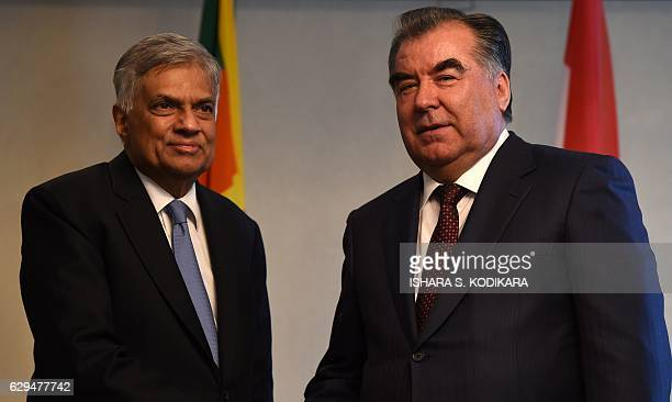 Sri Lankan Prime Minister Ranil Wickremesinghe shakes hands with the President of Tajikistan Emomali Rahmon as they pose for a photograph ahead of a...