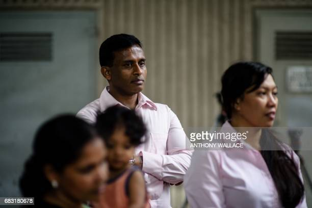Sri Lankan refugee Ajith Puspa and Filipino refugee Vanessa Rodel and Sri Lankan refugee Nadeeka look on after speaking with press outside the...