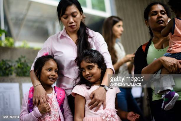 Sri Lankan refugee Nadeeka holds her baby boy Danath as her daughter Sethumdi stands with Keana daughter of Filipino refugee Vanessa Rodel as they...