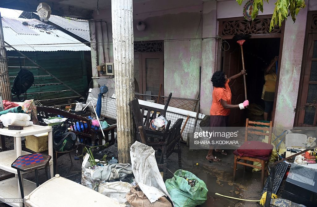 A Sri Lankan resident cleans the outside of her home following flooding in the Kolonnawa suburb of Colombo on May 24, 2016. Sri Lankans camped out in shelters in the capital face an uncertain future after massive flooding from torrential rain struck the island, forcing them to flee their inundated homes. Water levels in Colombo are slowly falling after the Kelani river running through the city of 650,000 burst its banks early last week, and a cleanup is underway. KODIKARA