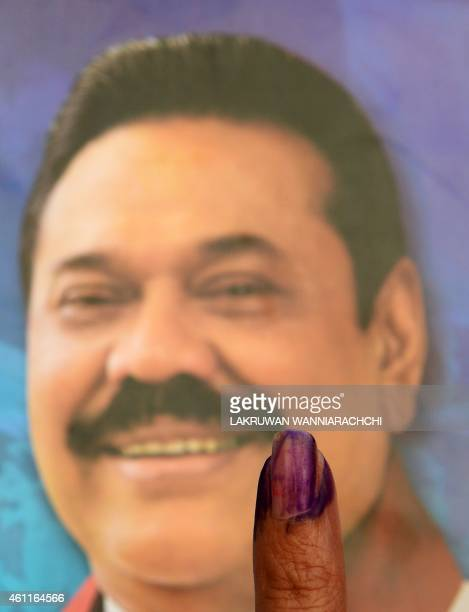 A Sri Lankan resident holds up her inked finger after voting in the country's presidential election at a polling station in the town of Tangalla some...