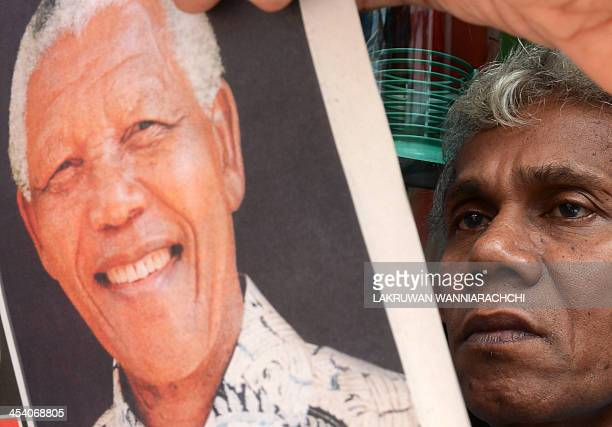 A Sri Lankan resident reads a newspaper carrying the image of South African former president Nelson Mandela and news of his death in Colombo on...