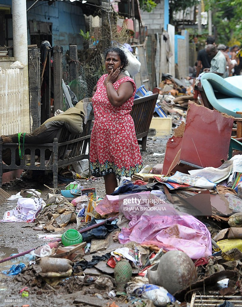 A Sri Lankan resident stands among debris following flooding in the Kolonnawa suburb of Colombo on May 24, 2016. Sri Lankans camped out in shelters in the capital face an uncertain future after massive flooding from torrential rain struck the island, forcing them to flee their inundated homes. Water levels in Colombo are slowly falling after the Kelani river running through the city of 650,000 burst its banks early last week, and a cleanup is underway. KODIKARA
