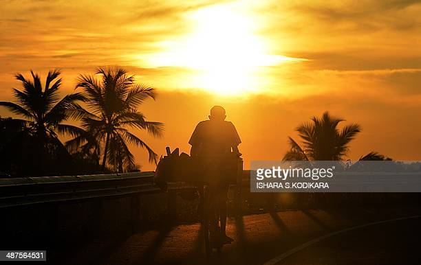 A Sri Lankan resident transports fish for sale on his bicycle in Colombo on May 1 2014 Sri Lanka's economy recorded 80 percentplus growth for two...