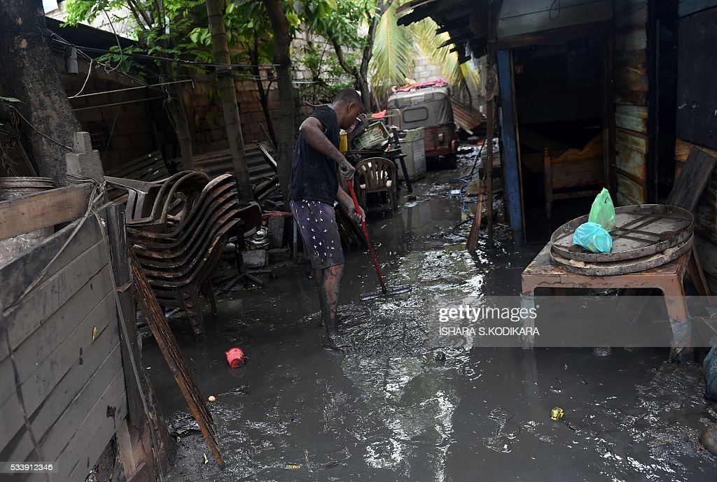 A Sri Lankan resident tries to clear away flood waters from outside his home in the Kolonnawa suburb of Colombo on May 24, 2016. Sri Lankans camped out in shelters in the capital face an uncertain future after massive flooding from torrential rain struck the island, forcing them to flee their inundated homes. Water levels in Colombo are slowly falling after the Kelani river running through the city of 650,000 burst its banks early last week, and a cleanup is underway. KODIKARA