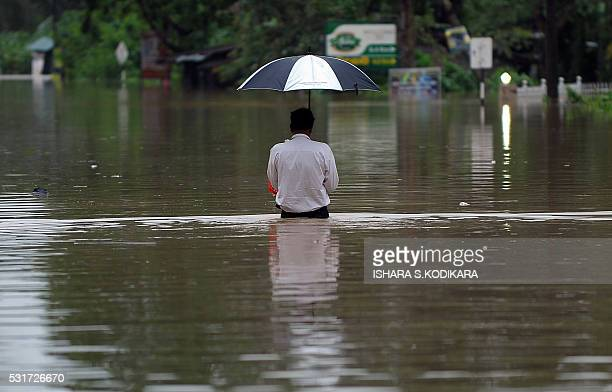 Sri Lankan resident wades through floodwaters in Pugoda on May 16 2016 Floods and landslides in Sri Lanka have killed at least eight people including...