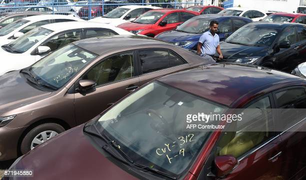 A Sri Lankan resident walks among cars at a vehicle sales centre in Colombo on November 9 2017 Vehicle sales had slowed in Sri Lanka in recent weeks...