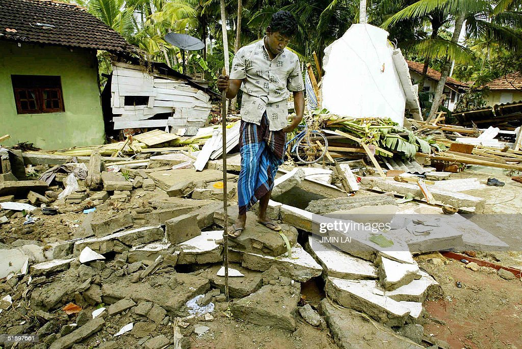 Sri Lankan resident walks on the rubble of his house in the southern coastal town of Matara 28 December 2004 after the region was hit by...