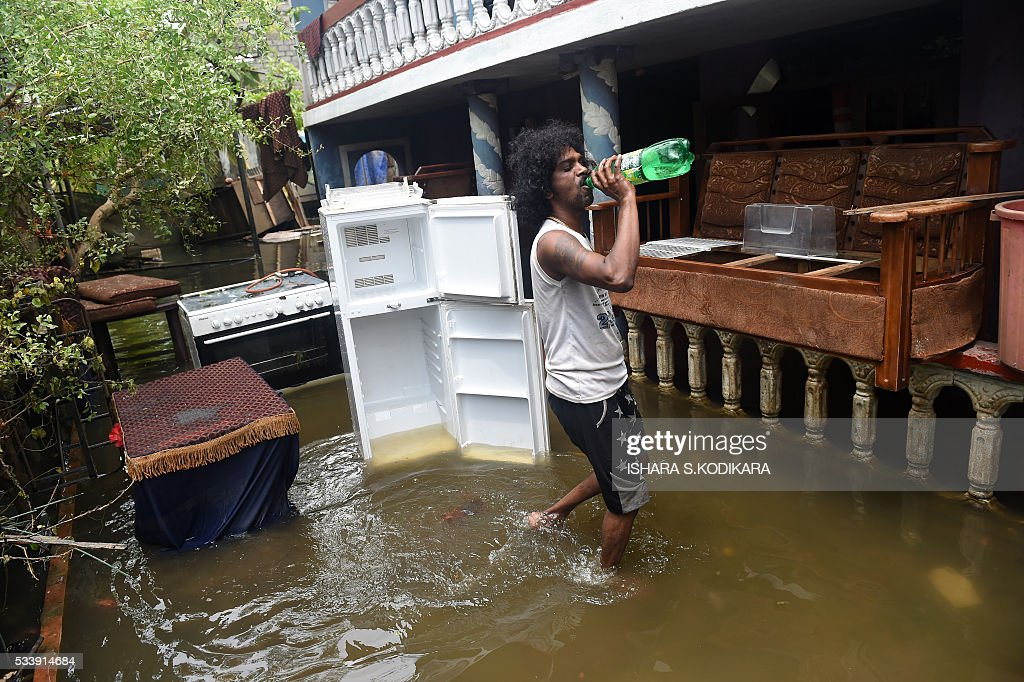 A Sri Lankan resident walks through floodwaters in the Kolonnawa suburb of Colombo on May 24, 2016. Sri Lankans camped out in shelters in the capital face an uncertain future after massive flooding from torrential rain struck the island, forcing them to flee their inundated homes. Water levels in Colombo are slowly falling after the Kelani river running through the city of 650,000 burst its banks early last week, and a cleanup is underway. KODIKARA