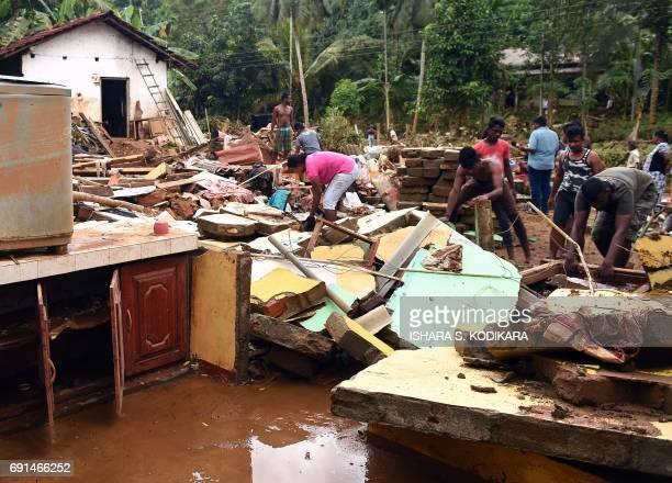 Sri Lankan residents clear debris from damaged homes following flooding in Yatagampitiya village in Bulathsinhala on June 2 2017 Sri Lanka pledged...