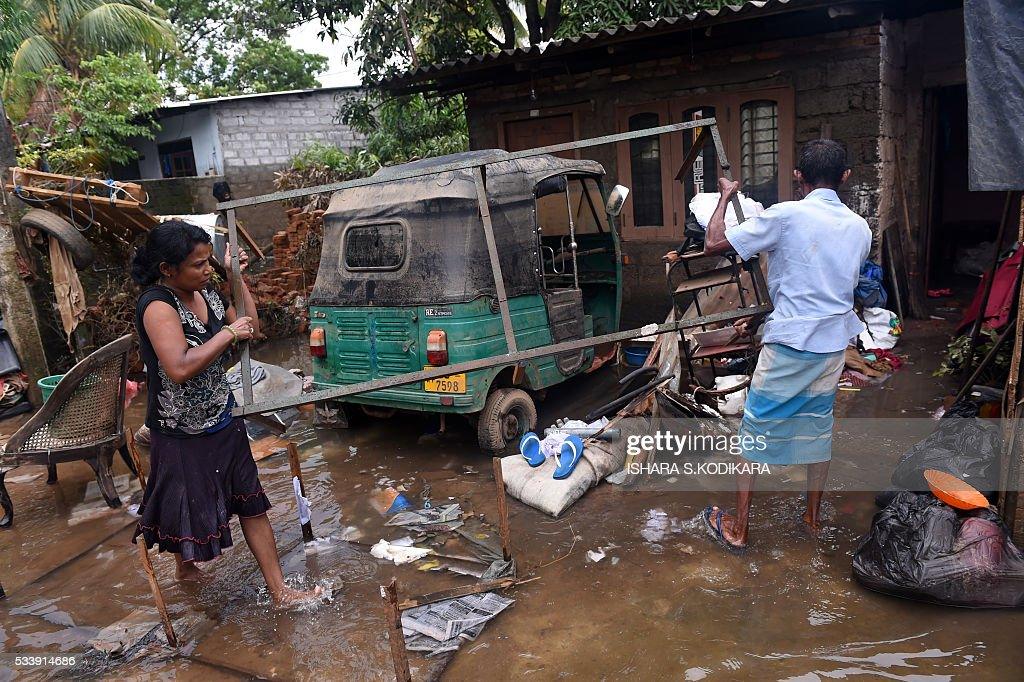 Sri Lankan residents clear debris from outside homes following flooding in the Kolonnawa suburb of Colombo on May 24, 2016. Sri Lankans camped out in shelters in the capital face an uncertain future after massive flooding from torrential rain struck the island, forcing them to flee their inundated homes. Water levels in Colombo are slowly falling after the Kelani river running through the city of 650,000 burst its banks early last week, and a cleanup is underway. KODIKARA