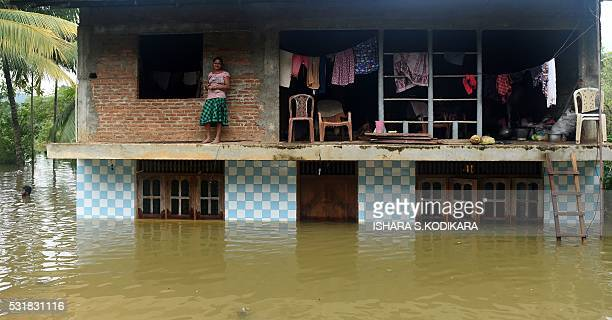 TOPSHOT Sri Lankan residents look out from their home inundated by floodwaters in Pugoda about 35 kms from capital Colombo on May 17 2016 Heavy rains...