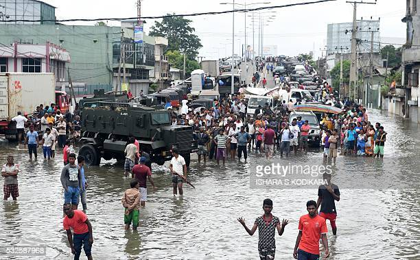 Sri Lankan residents make their way through floodwaters in Colombo on May 19 2016 Sri Lankan troops recovered seven more bodies from piles of mud on...