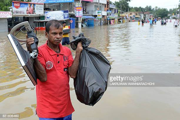 Sri Lankan residents make their way through floodwaters in the suburb of Kaduwela in capital Colombo on May 17 2016 Emergency workers in Sri Lanka on...