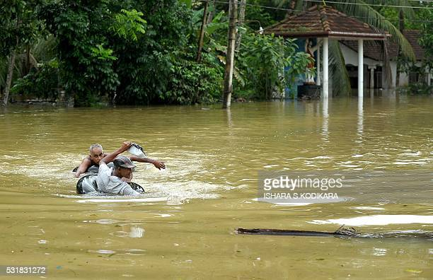 Sri Lankan residents padddle on inflated tubes through the floodwaters in Pugoda about 35 kms from capital Colombo on May 17 2016 Heavy rains claimed...