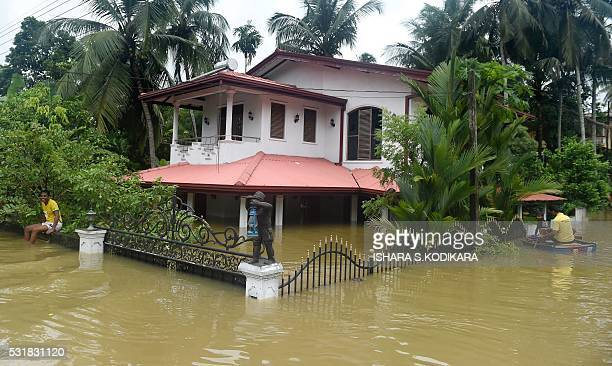 Sri Lankan residents paddle around their home inundated by floodwaters in Pugoda about 35 kms from capital Colombo on May 17 2016 Heavy rains claimed...