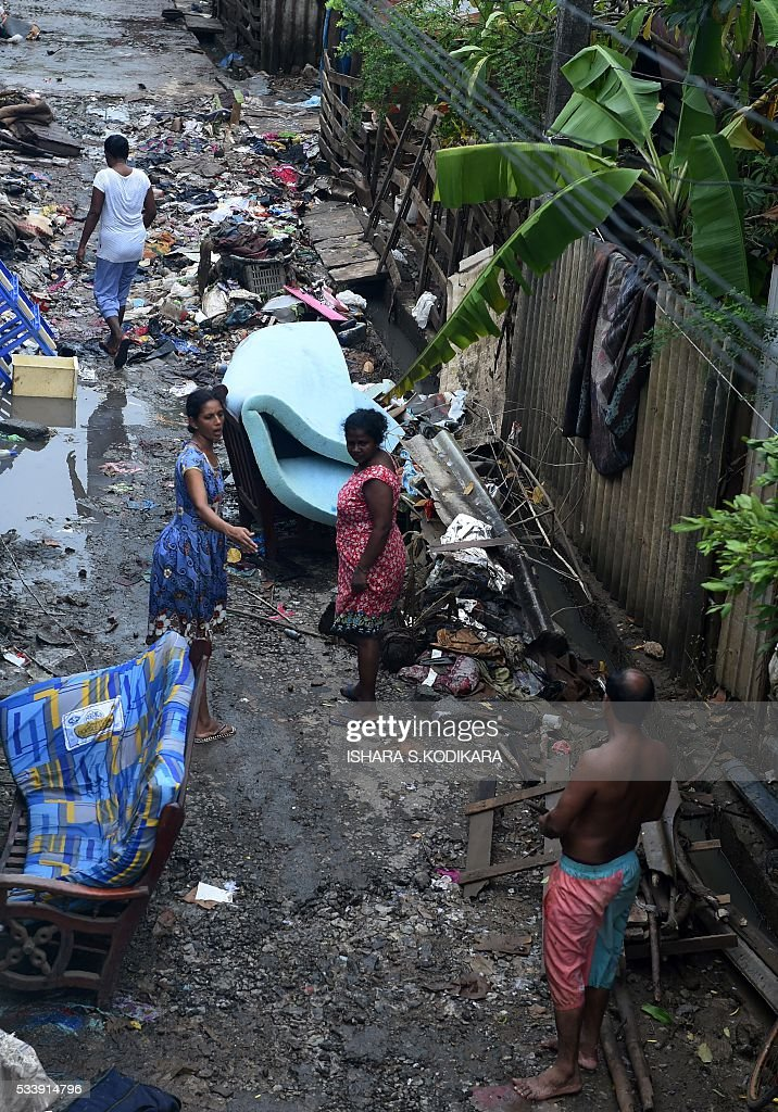 Sri Lankan residents stand among debris following flooding in the Kolonnawa suburb of Colombo on May 24, 2016. Sri Lankans camped out in shelters in the capital face an uncertain future after massive flooding from torrential rain struck the island, forcing them to flee their inundated homes. Water levels in Colombo are slowly falling after the Kelani river running through the city of 650,000 burst its banks early last week, and a cleanup is underway. KODIKARA
