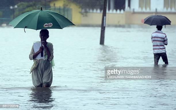 Sri Lankan residents wade through floodwaters after heavy rains in Colombo on May 16 2016 Floods and landslides in Sri Lanka have killed at least...