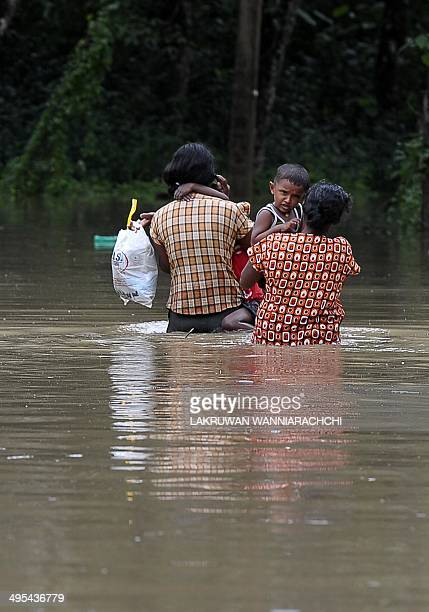 Sri Lankan residents wade through floodwaters in Matugama some 64 kms south of Colombo on June 3 2014 after heavy monsoon raIns caused havoc in the...