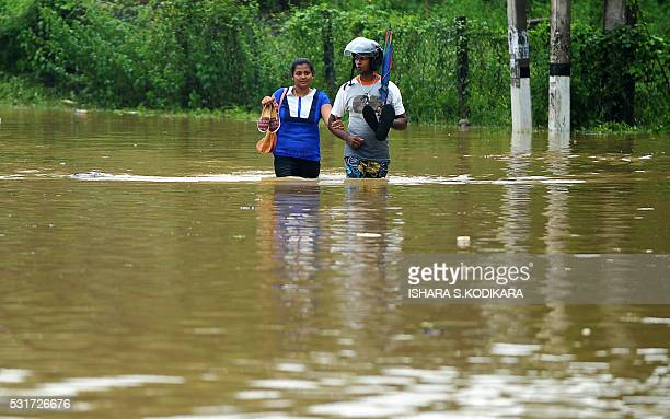 Sri Lankan residents wade through floodwaters in Pugoda on May 16 2016 Floods and landslides in Sri Lanka have killed at least eight people including...