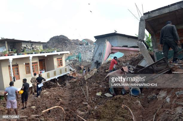 Sri Lankan residents walk through damaged homes at the site of a collapsed garbage dump in Colombo on April 15 2017 The death toll from a collapsed...