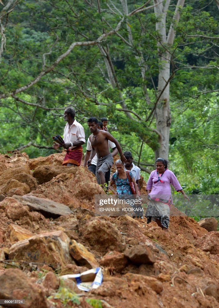 Sri Lankan residents walk through the site of a mudslide in the Kiribathgala village in Ratnapura district on May 31, 2017. Sri Lanka pledged May 31 to tighten construction laws as the toll from heavy rains rose to 203, saying many landslide victims would have survived had their homes not been built on slopes. The government will also prosecute anyone violating existing rules by building on landslide-prone slopes, said Disaster Management Minister Anura Yapa. /