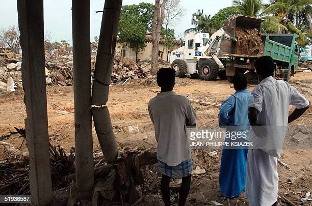 Sri Lankan residents watch a bulldozer clearing the rubble of destroyed houses 11 January 2005 in Mullaitivu in the rebel Liberation Tigers of Tamil...