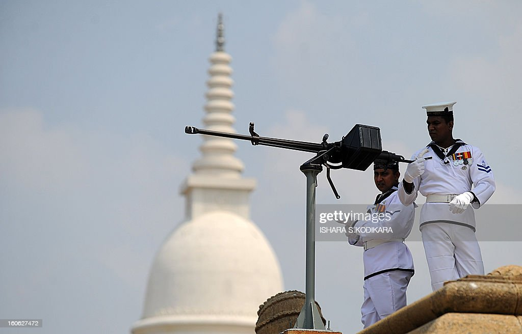 Sri Lankan sailors man a machine gun as other personnel fire a 21-gun salute on the capital's seafront Galle Face promenade to mark the island nation's 65th Independence Day in Colombo on February 4, 2013. Sri Lanka marked its freedom anniversary with a thinly veiled denunciation of Western moves to pass a new resolution against the island at the UN Human Rights Council. AFP PHOTO/Ishara S.KODIKARA