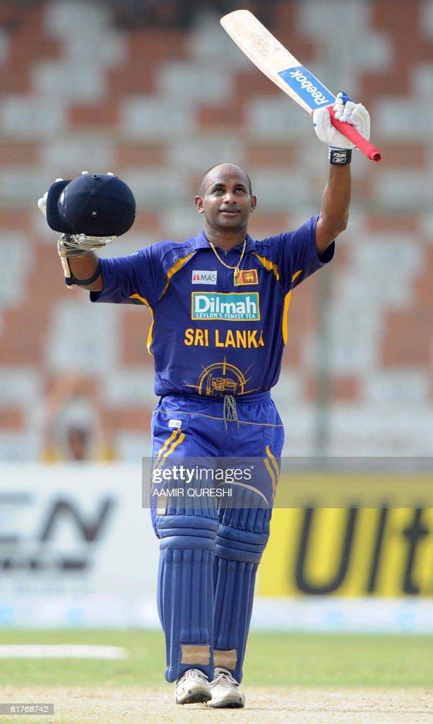 Sri Lankan Sanath Jayasuriya raises his bat and helmet after he scored a century against Bangaladesh during the Super League Asia Cup match between...