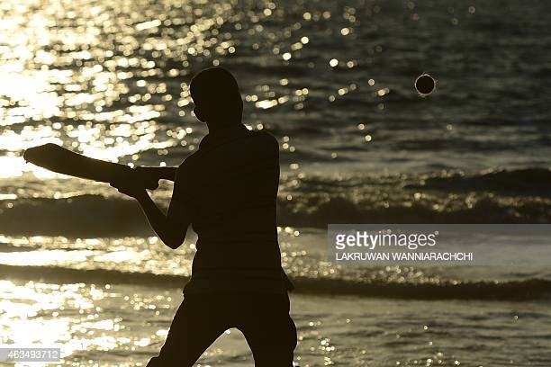 A Sri Lankan schoolboy plays cricket on a beach at sunset in Colombo on February 15 2015 Sri Lanka's youth population aged 10 to 19 make up some 15...