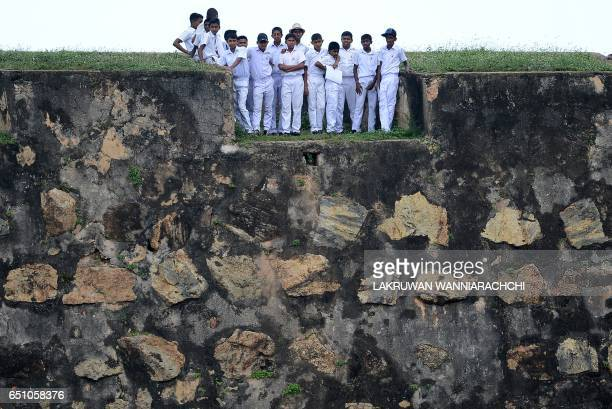 TOPSHOT Sri Lankan schoolchildren on top of a 14th century Dutch fort near the Galle International Cricket Stadium watch the fourth day of the...