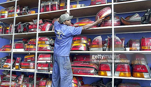 Sri Lankan shop assistant Prasad Kumara selects tail lamps at the Yunikon International used car spare parts store 07 January 2006 in the...