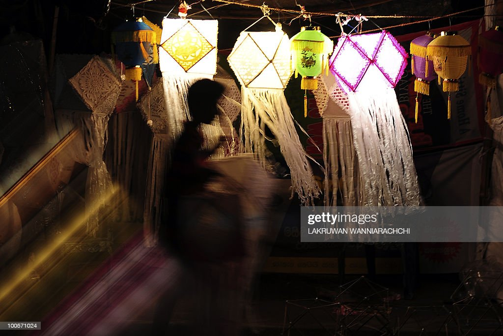 A Sri Lankan shop owner hangs lanterns for sale at his temporary shop in Colombo on May 25, 2010, ahead of the key Buddhist festival of Wesak. Buddhists commemorates the birth of Buddha, his attaining enlightenment and his passing away on the full moon day of May which falls on May 27 this year. AFP PHOTO/Lakruwan WANNIARACHCHI