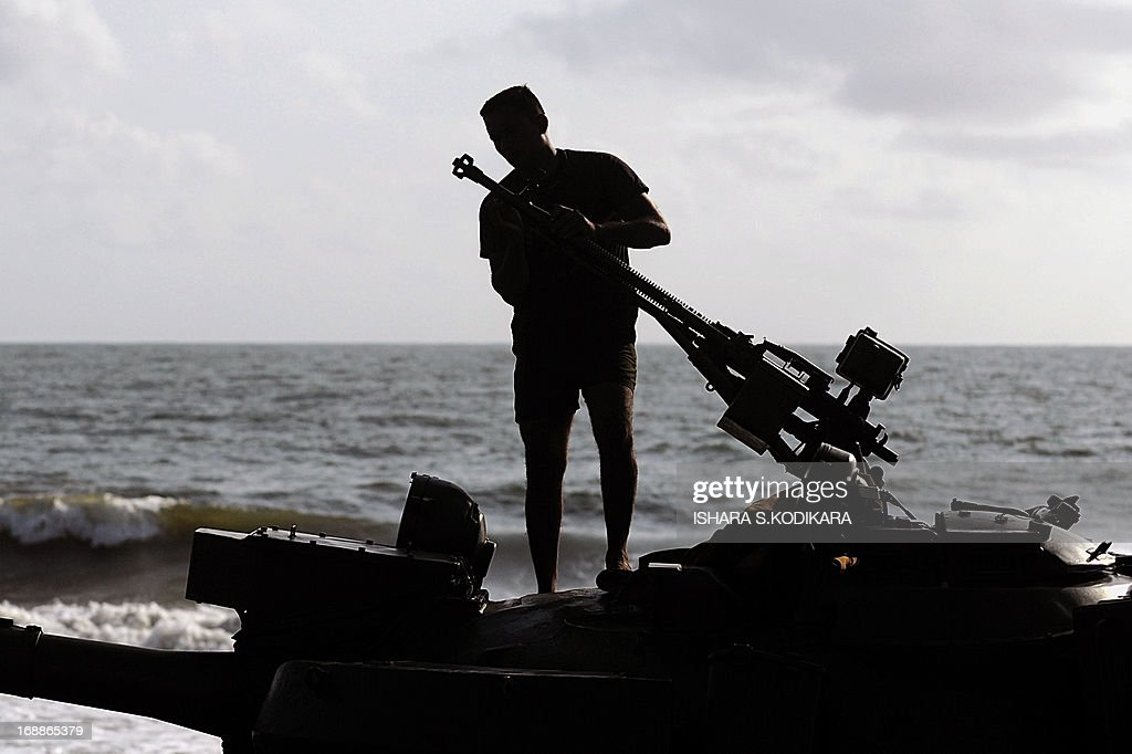 A Sri Lankan soldier cleans a gun on top of a tank following a Victory Day parade rehearsal in Colombo on May 16, 2013. Sri Lanka celebrates War Heroes month with a military parade scheduled for May 18. The parade celebrates the fourth anniversary of the military defeat of the Tamil Tiger rebels in May 2009, ending a 37-year long separatist conflict. AFP PHOTO/ Ishara S. KODIKARA