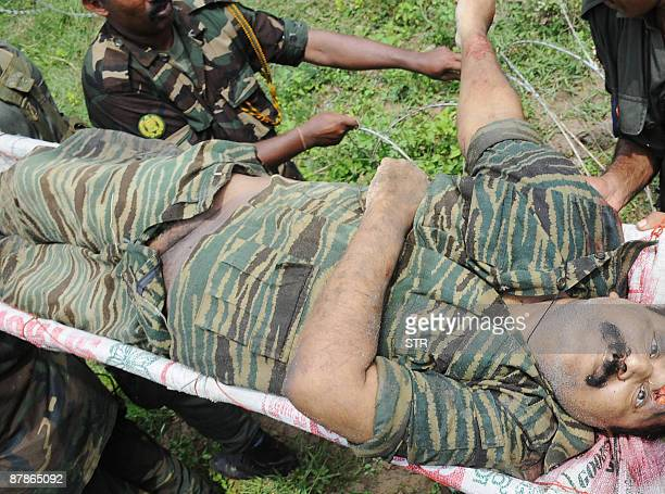 Sri Lankan soldiers carry the remains of what is said to be Tamil Tiger rebel leader Velupillai Prabhakaran in the district of Mullaittivu on May 19...
