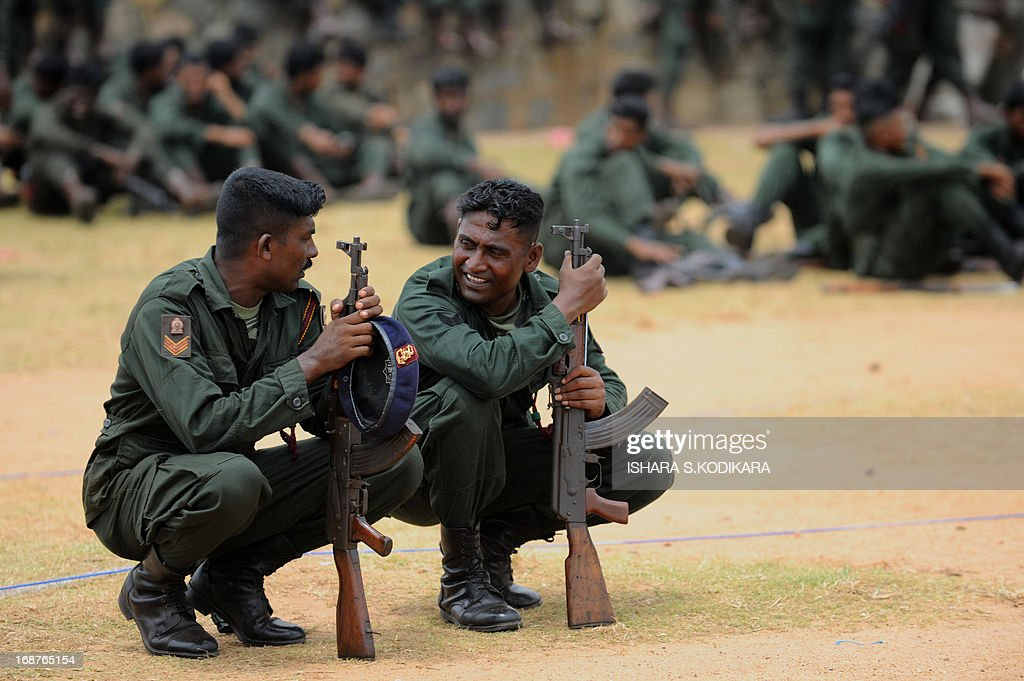 Sri Lankan soldiers rest during a Victory Day parade rehearsal in Colombo on May 15, 2013. Sri Lanka celebrates War Heroes month with a military parade scheduled for May 18. The parade celebrates the fourth anniversary of the military defeat of the Tamil Tiger rebels in May 2009, ending a 37-year long separatist conflict. AFP PHOTO/ Ishara S. KODIKARA