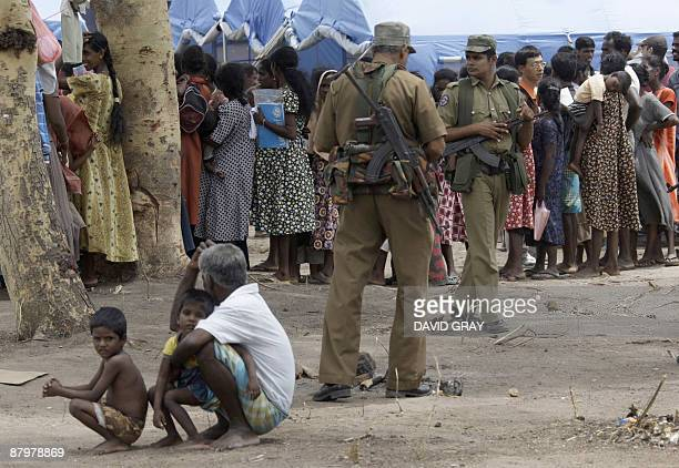 Sri Lankan soldiers stand next to Tamil civilians as they stand in line to receive food in the Manik Farm refugee camp located on the outskirts of...