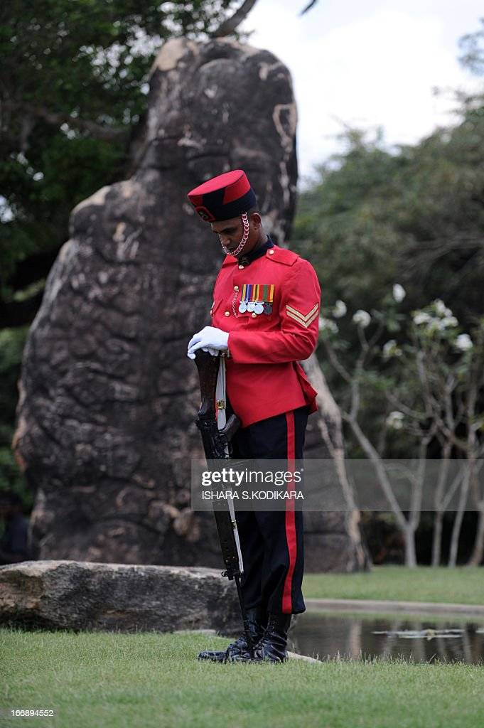 A Sri Lankan solider bows his head at a monument during a ceremony commemorating fallen soldiers in the eastern region of Thoppigala on April 18, 2013. The monument commemorated government troops killed while wresting control over the region from Tamil Tiger rebels during the war. AFP PHOTO/ Ishara S. KODIKARA