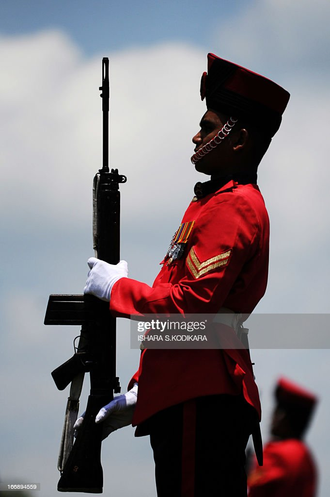 A Sri Lankan solider stands at attention at a monument during a ceremony commemorating fallen soldiers in the eastern region of Thoppigala on April 18, 2013. The monument commemorated government troops killed while wresting control over the region from Tamil Tiger rebels during the war. AFP PHOTO/ Ishara S. KODIKARA