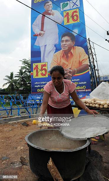 A Sri Lankan street vendor cooks corn on the cob in front of an election billboard of Sri Lankan President Mahinda Rajapakse's younger brother Basil...