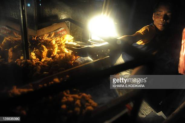 A Sri Lankan street vendor selling prawns fried chicken and bread waits for customers at the coastal promenade in the island's northern town of...