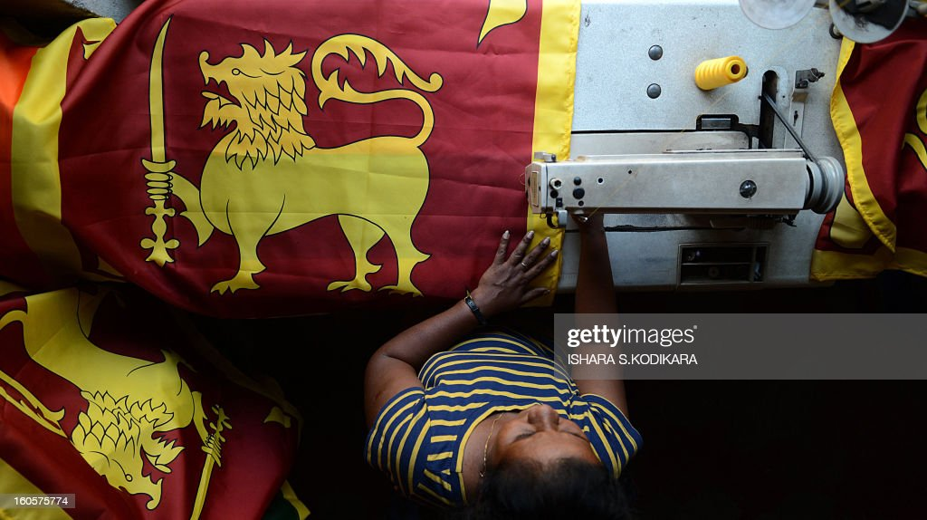 A Sri Lankan tailor stitches national flags at a shop in Colombo on February 3, 2013, ahead of Independence Day. Sri Lanka will celebrate its 65th national day on February 4. AFP PHOTO/Ishara S.KODIKARA