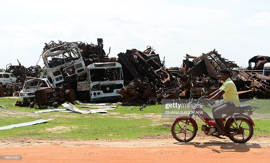 A Sri Lankan Tamil man rides his motorcycle past a wreckage of vehicles in Mullaittivu on November 2, 2012. A storm surge in Sri Lanka's northeast has exposed buried artillery guns of Tamil Tiger rebels in a region where the final battles of the country's 37-year conflict were fought, the army said. Troops stumbled on four 152mm artillery barrels and one 130 mm piece believed to have been used by Tiger guerrillas during their last stand in the district of Mullaittivu, army spokesman Ruwan Wanigasooriya said. AFP PHOTO/ Ishara S. KODIKARA